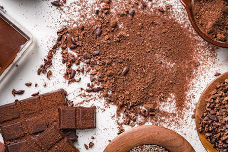 Cocoa beans pods, chocolate bar pieces, cocoa powder, Ingredients to making chocolates.