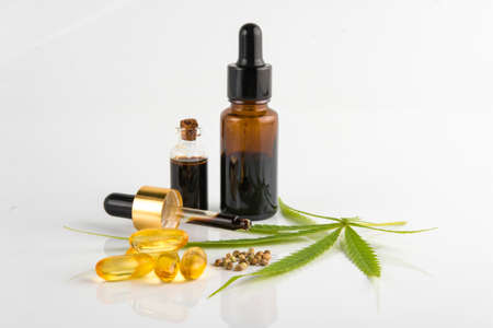 hemp essential oil in small glass bottle. container with cannabis leaves and cannabis seeds on white background. 版權商用圖片