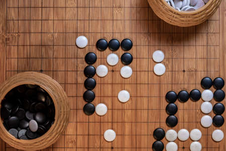 Go board game playing. A competitor is placing a marble piece on a Go board game, Hand playing black and white stone pieces on