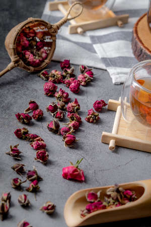 tea made from tea rose petals in a glass bowl on drak black rustic background, Concept tea time. Imagens