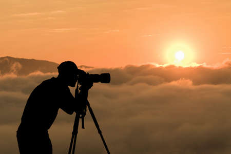 Man Silhouette Photographer take photo on hill high mountain professional camera shooting photo landscape sunset on top mountain nature twilight sky background. Imagens