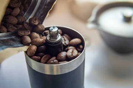 Coffee beans in a hand grinder, Pour roasted coffee beans into a manual coffee grinder.
