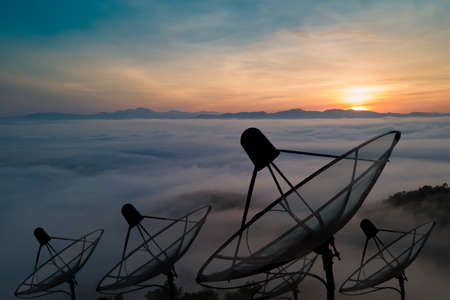 Big black satellite dish on Beautiful spiral sunset sky background, transmission data. digital technology sky background.