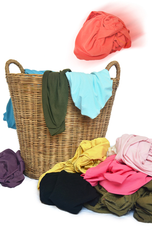 toss: Toss shirt in wicker basket and  pile of colorful shirts