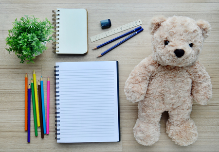 Artistic : Blank paper, color paint and bear doll on the wood table - Top view photo