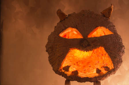 hollows: Halloween pumpkin with a light into the shadows, orange-yellow background.
