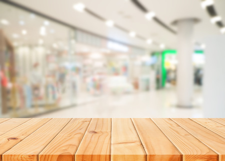 supermarket: Wooden table in front of abstract blurred shopping mall background. For present your products.