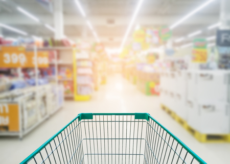Supermarket store abstract blur background with shopping cart, Supermarket aisle with empty shopping cart