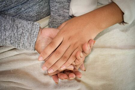 Close up granddaughter takes care of the health sick grandmother at home by holding hands. Lifestyle support the love of the family. Archivio Fotografico