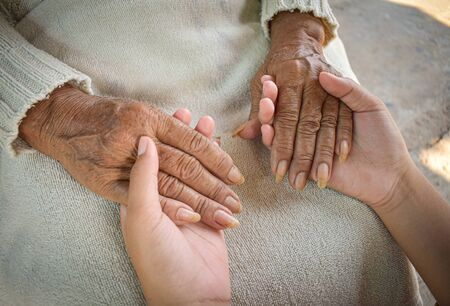 Close up granddaughter takes care of the health sick grandmother at home by holding hands. Lifestyle support the love of the family.