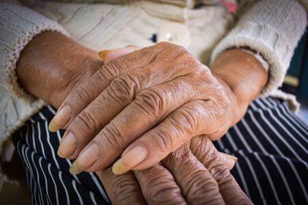 la main de la vieille femme malade repose sur les genoux. Soins de santé mentale à domicile.