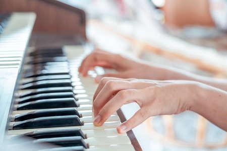 Female pianist hands on grand piano keyboard.