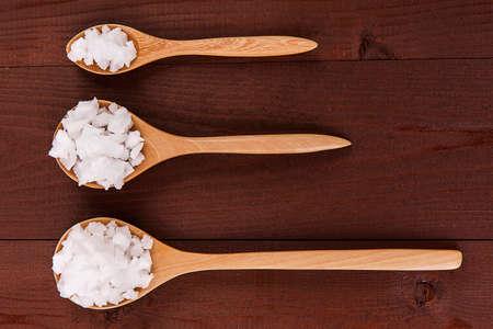 rock salt: Sea rock salt on spoons on wood background