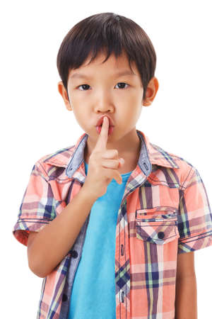 hushing: cute asian boy with his finger over her mouth, hushing.