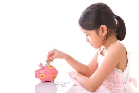 gain money: Petite fille insert pièce de monnaie dans la tirelire sur fond blanc