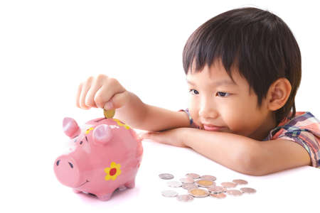 coin bank: Little boy insert coin into piggy bank on white background Stock Photo