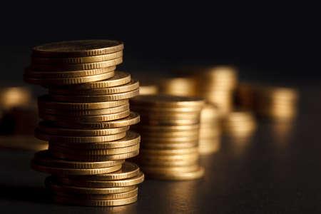 Pila di moneta d'oro su sfondo nero.