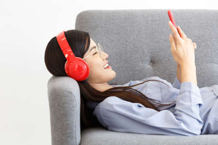 Side View of Happy cheerful Asian woman wearing wireless headphones listening to music from smartphone lay down on Sofa. Фото со стока