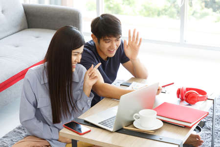 Young couple business people making Video Call. working Online Business on Messing Table. Work From Home Concept.