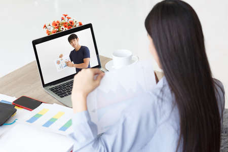 Young man and Young woman showing Chart while Presentation on Video Call. Work For Home. Фото со стока