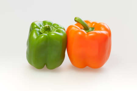 capsicum: Green and orange capsicum or sweet pepper on white background