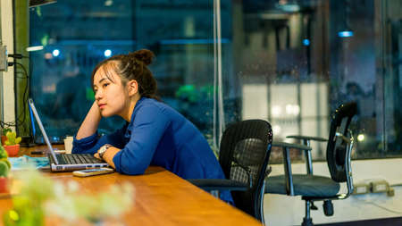 working overtime: Young woman working at a laptop in the office at night time. Business woman - office worker. Bored young woman sitting at her desk in front of laptop. She is working overtime. Selective focus.