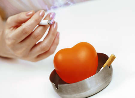 Orange heart in  ashtray and a woman photo