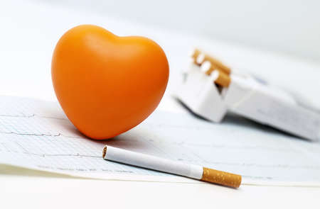 Orange heart, cigarettes and the cardiogram. photo