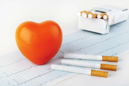 Red heart on the cardiogram and cigarettes.  photo