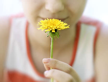 A young girl holds a yellow dandelion  Stock Photo - 13759116