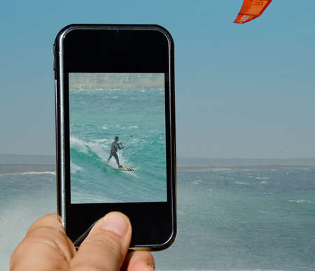 Hand holding a mobile phone taking picture of a kitesurfer Stock Photo