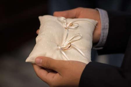 Best man holding wedding rings on the white silk pillow. Stock Photo