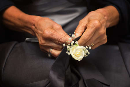 Hands of mother who sew flowers on the groom