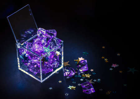 Plastic box filled with gems and stars Stock Photo