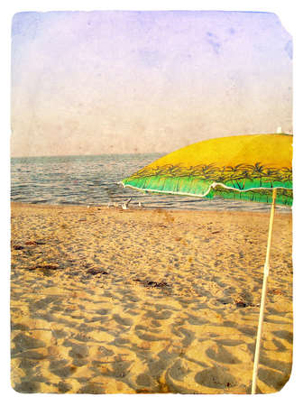 Seascape with umbrella. Old postcard, design in grunge and retro style photo