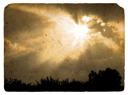 Beams of the sun closed by a cloud. Old postcard, design in grunge and retro style photo