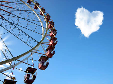 Cloud in the form of hearts and a Ferris wheel on the blue clear sky photo