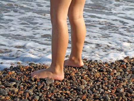 naked child: Barefoot child on the wet coastal shingle. Disease prevention feet, flat feet  Stock Photo