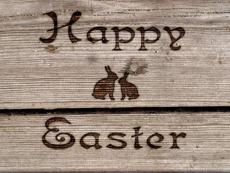 Happy Easter - burned an inscription on a wooden surface.