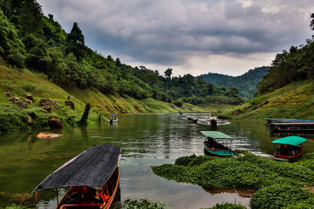 Passenger boats for tourism are parked in the river on sunset background at Khun Dan Prakarnchon Dam Banco de Imagens
