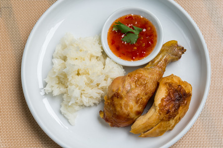 Thai style bbq chicken with sticky rice and sweet chili dipping sauce on the white plate