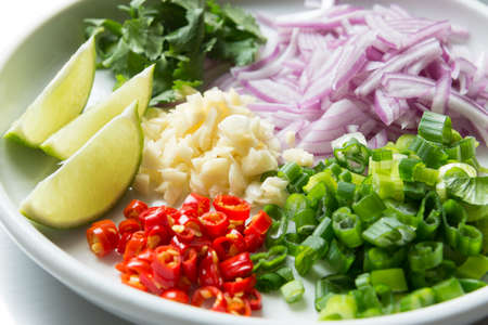 scallion: a close-up look of chopped up red chili, garlic, scallion, red onion, cilantro and lime