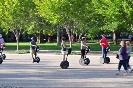 a two wheeled vehicle: Washington DC, USA - October 10,2011: Group of tourists cruising around on Segway(battery-powered electric vehicle) near the White House which located in Washington  DC capital city of United States of America