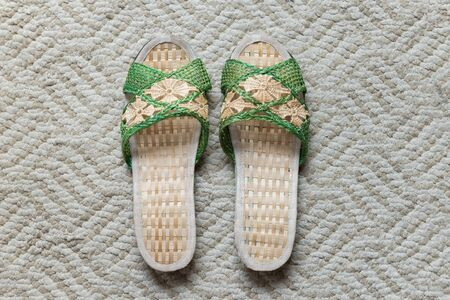 green hand: a pair of light brown and green hand weaved woman slipper on a light grayish brown area rug Stock Photo