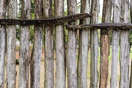 stake: aged round wooden fence that can see through in between each stake Stock Photo
