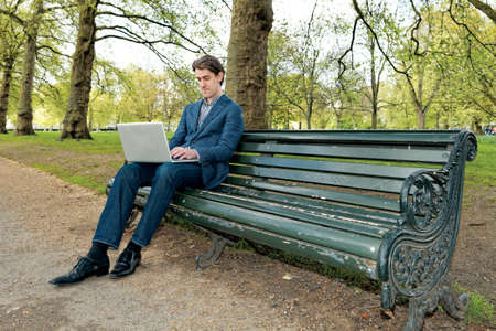 Businessman working with laptop in park photo