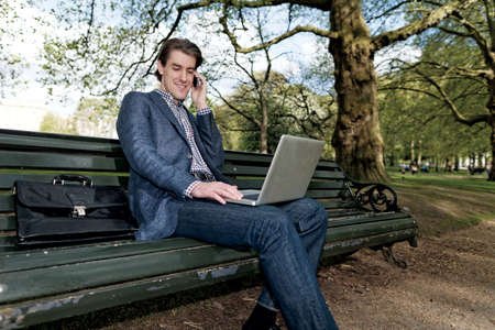 Businessman talking on the phone while working on his laptop photo