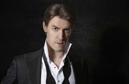 untied: Elegant man in tuxedo with untied bow, dark background