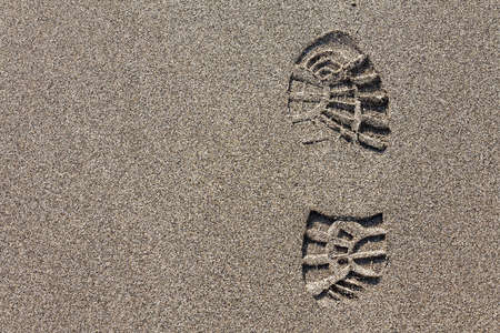 Imprint of the hiking boot on sand with copy space