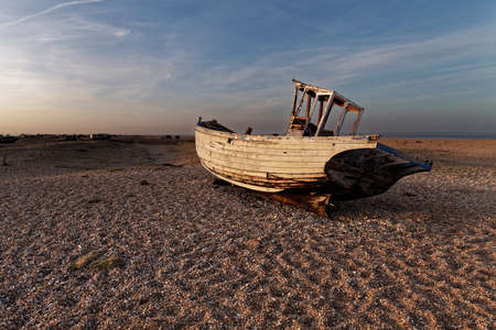 shingle: Empty shingle beach with old, abandoned fishing boat